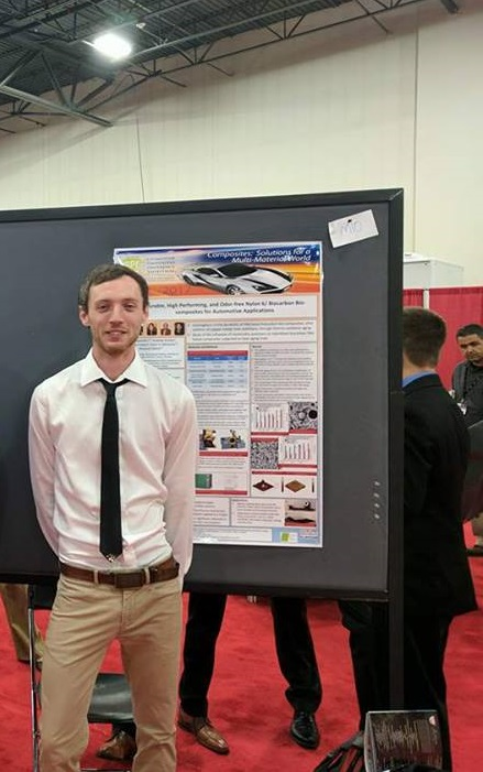 Dylan Jubinville standing in front of his SPE ACCE poster.